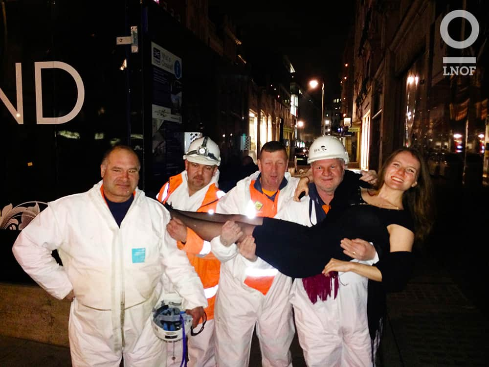 Four men in white sewer suits, holding a woman in a black dress in the streets