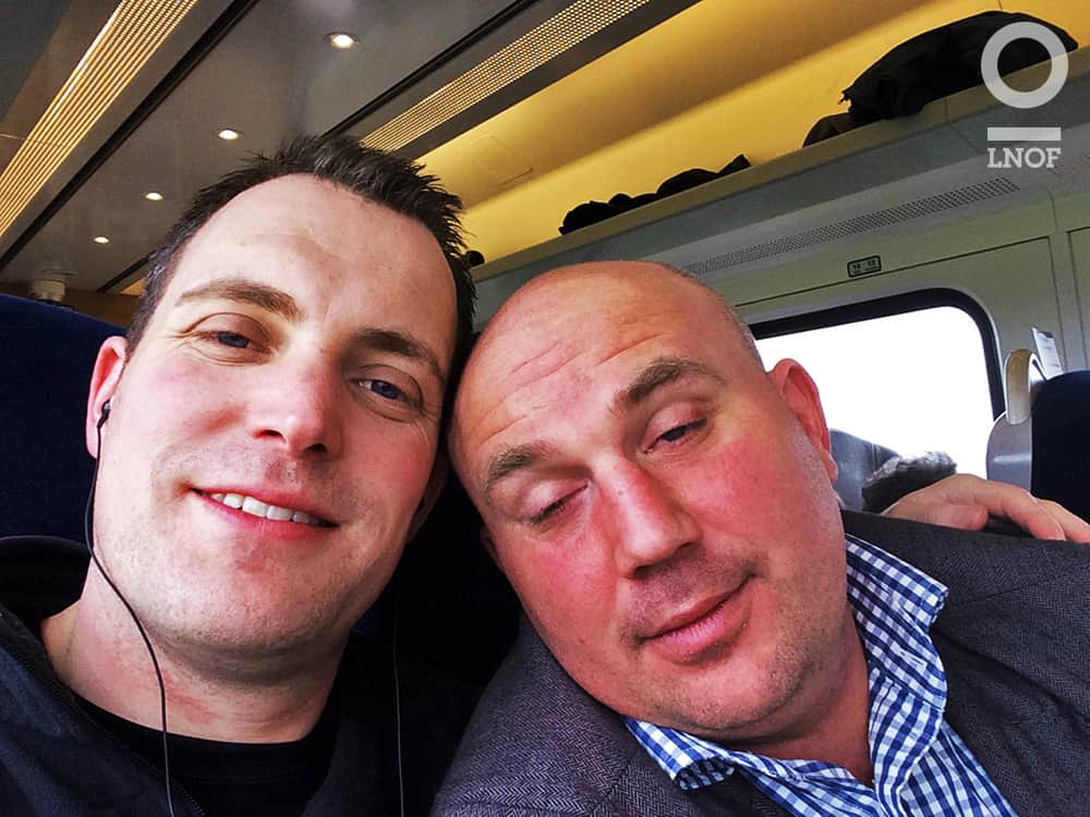 Two men posing for a selfie on a train
