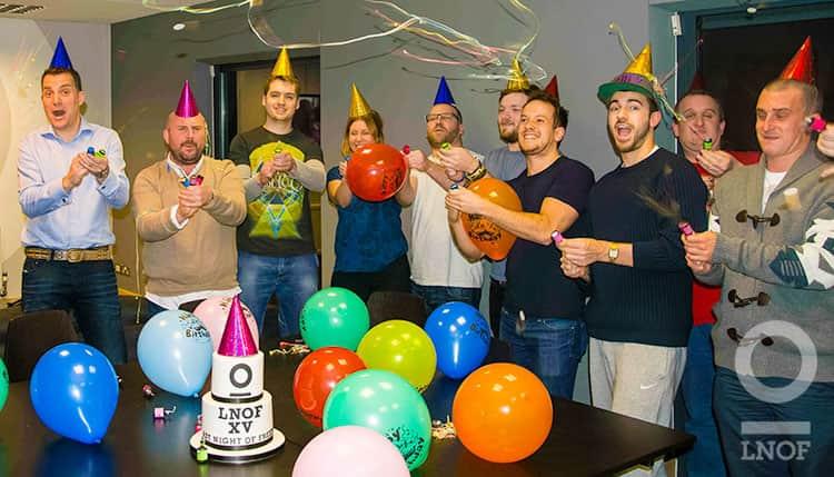People firing party poppers in party hats in a room