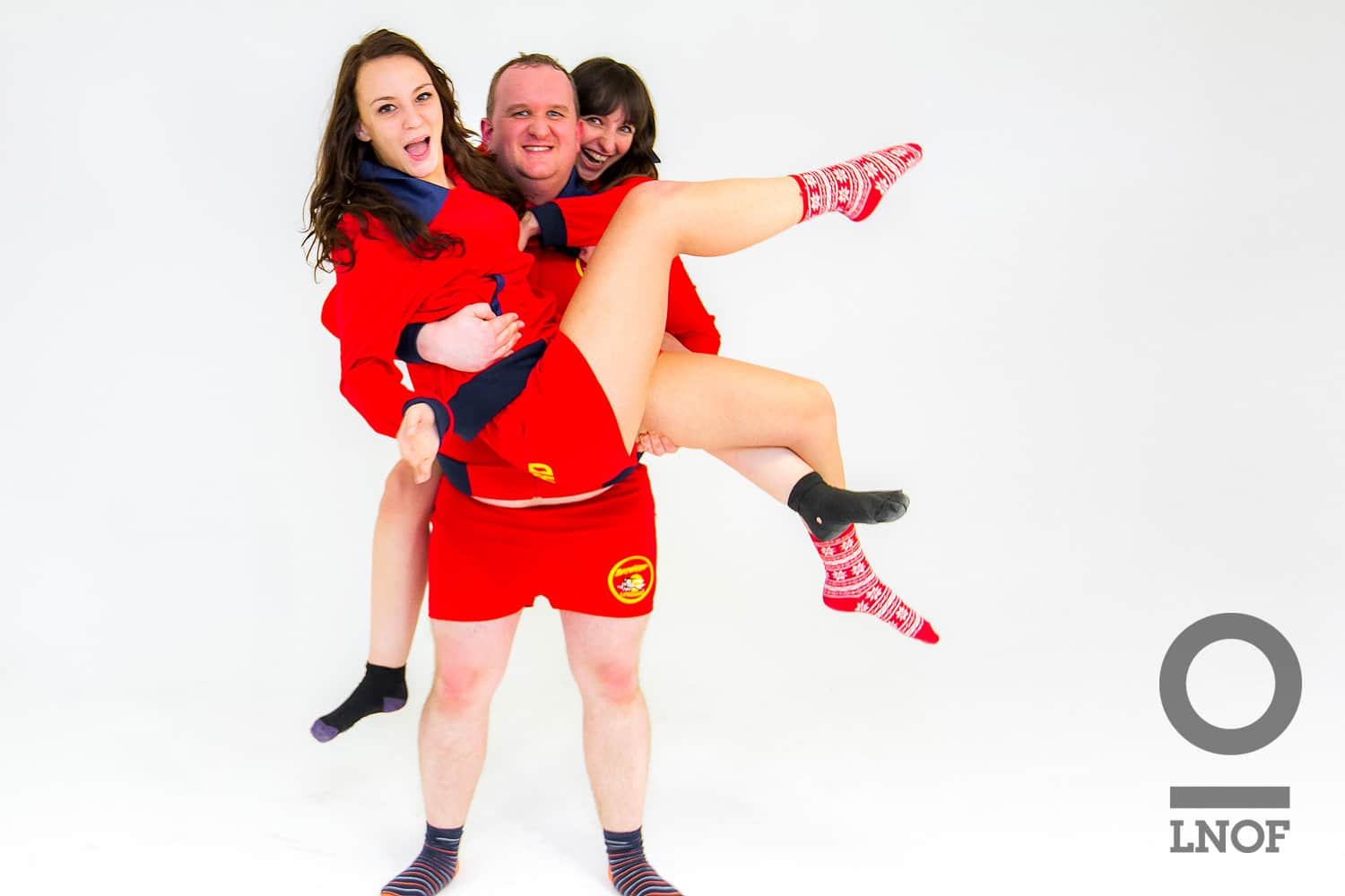 Lifeguard carrying two other colleagues in his Baywatch outfit