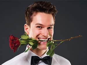 man with rose between teeth