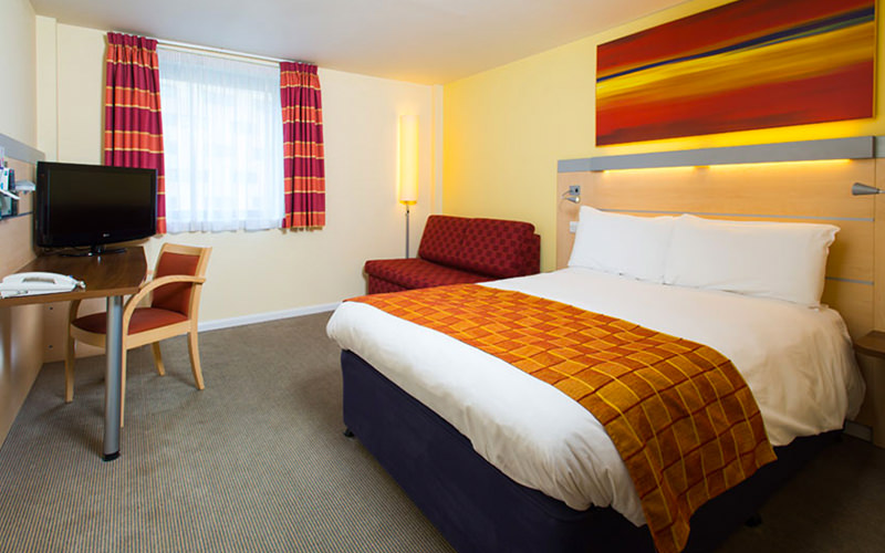 A double bed made up with an orange throw on top, in a hotel room, and facing a desk