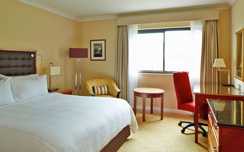 A white double bed in a hotel room, placed next to a chair, and facing a red desk and desk chair