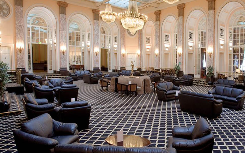 Leather sofs and tables in a hotel lobby, with two gold chandeliers above