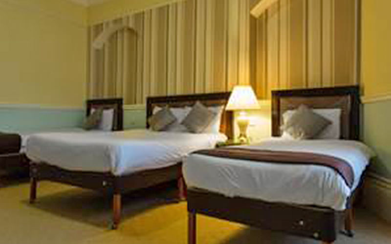 Three dark wooden beds in a room within The Carrington Hotel, Bournemouth