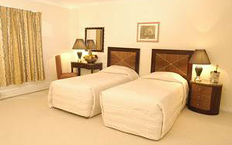 Two beds in a cream room within The Carrington Hotel
