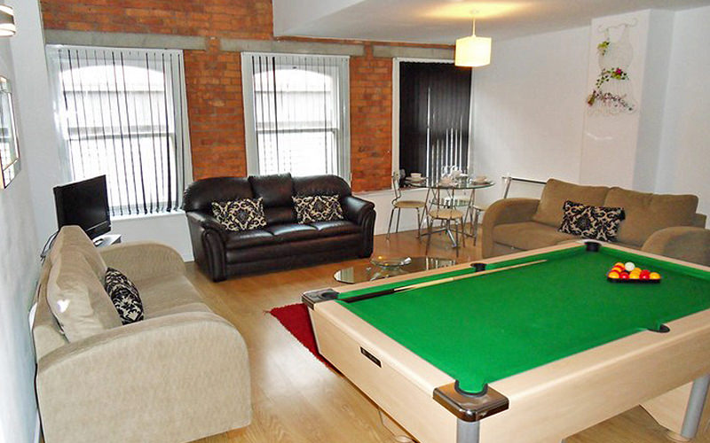 A pool table alongisde three leather sofas and a flat screen TV