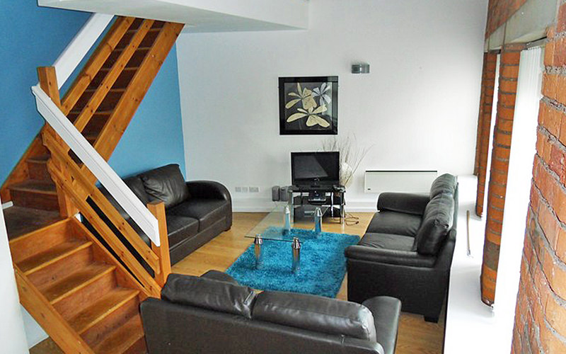 Three leather sofas, with a glass coffee table in the middle, facing a flat screen TV