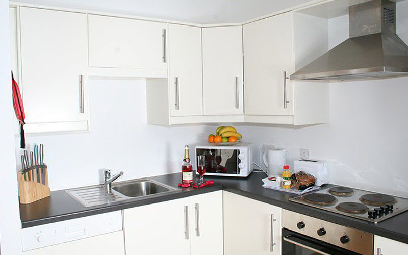 A white kitchen, with appliances placed on the counters alongisde an open bottle of red wine