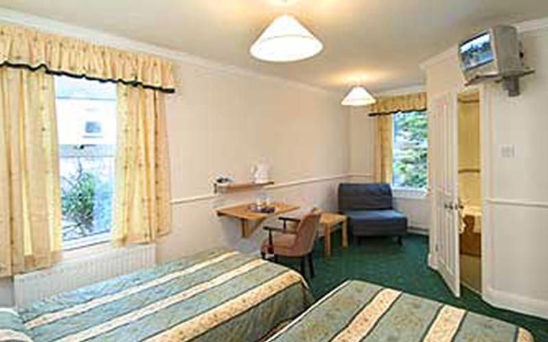 Two single beds in a hotel room, with a desk and chairs in the background