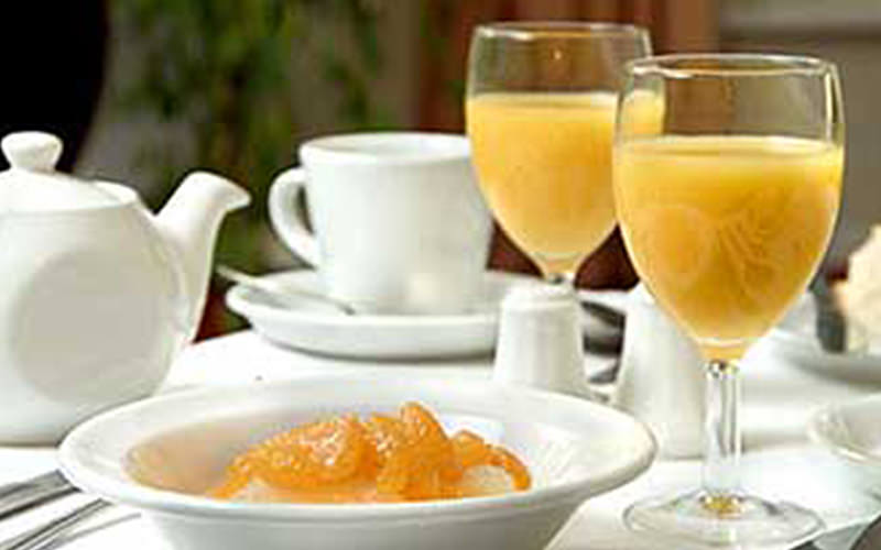 Two wine glasses with orange juice in, on a table set up for breakfast, alongside a bowl of food