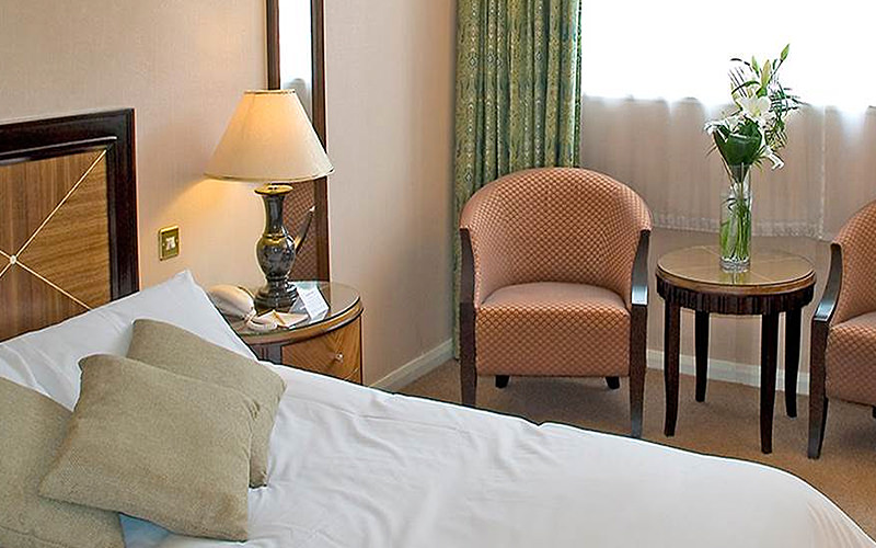 A double bed in a hotel room, with cushions placed on top, alongside a dressing table, and two chairs with a table in between
