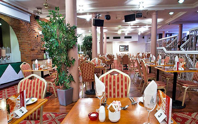 Three lines of tables and chairs set up for dinner in the restaurant at the Britannia Hotel, Manchester