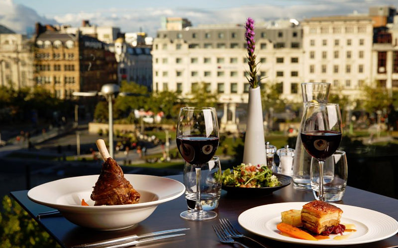 Two plates of food and two glasses of wine on a table, with buildings in the background