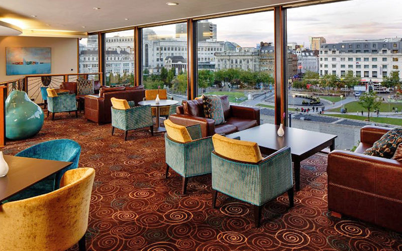 Tables and chairs facing the floor to ceiling windows in a lounge area at the Mercure Manchester
