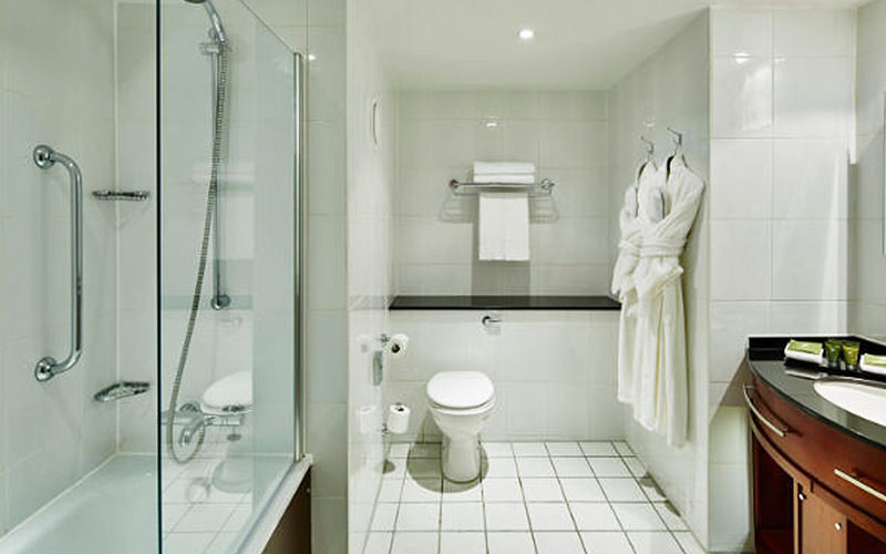 A white tiled bathroom, with a shower and sink on the sides of the walls