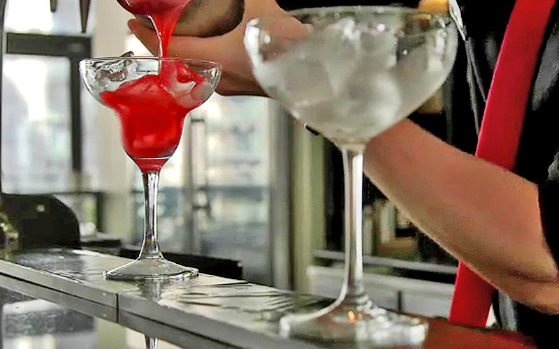 A red cocktail being poured out, with a cocktail in front