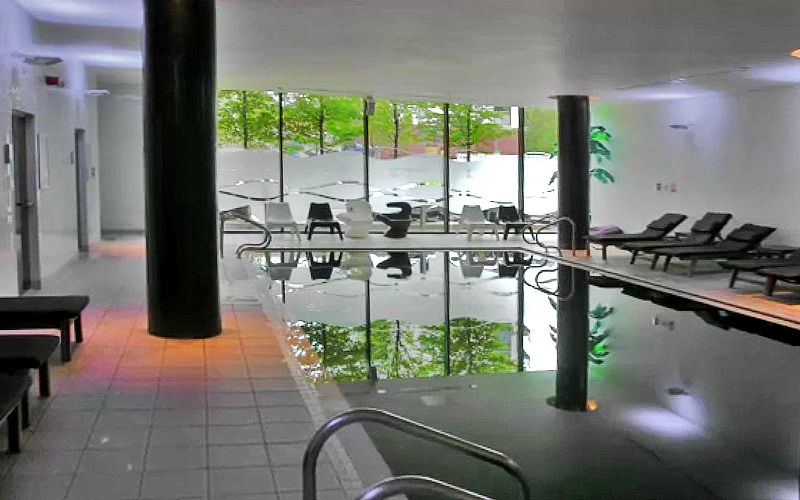 An indoor swimming pool, surrounded by black and white sun beds