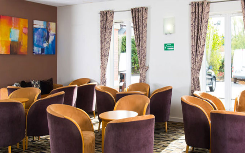 Tables and purple chairs in a room at the Holiday Inn Express, Manchester
