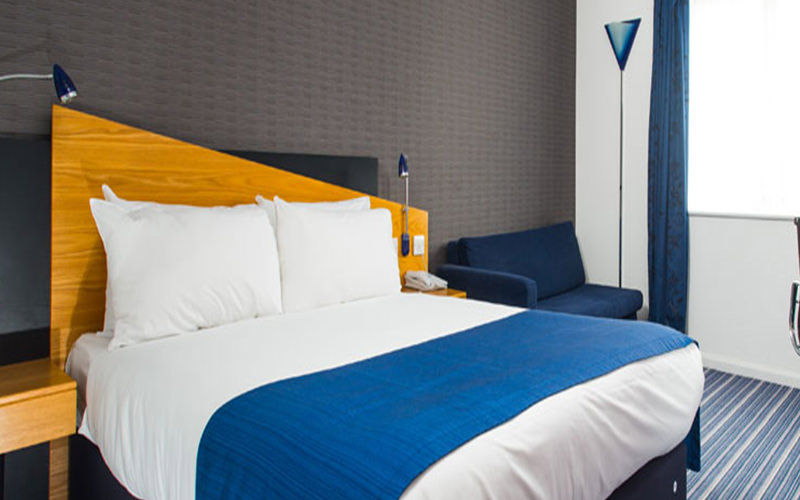 A double bed with a blue throw placed on top, next to a blue sofa in a hotel room