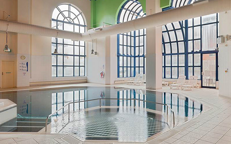 An indoor swimming pool in a white room, with large, blue arched windows