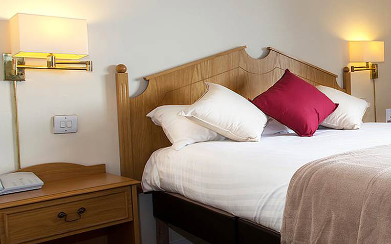 A double bed made up with cushions on top, and placed next to a bedside table
