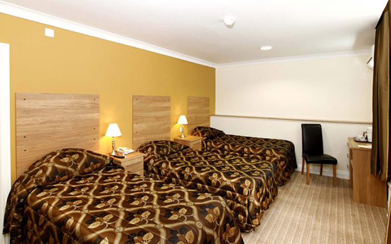 Three single beds in a mustard yellow hotel room, with a desk in the corner of the room