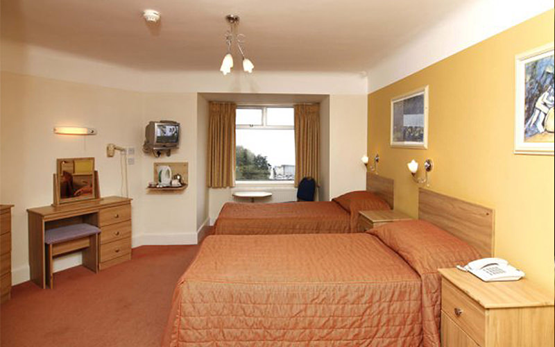 Two double beds in a mustard yellow hotel room, facing a dressing table