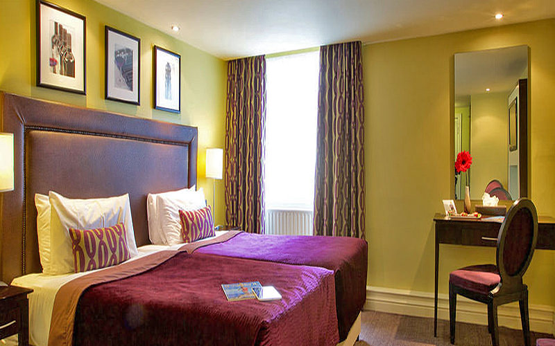 Two purple single beds in a yellow hotel room, facing a dressing cabinet with a purple chair