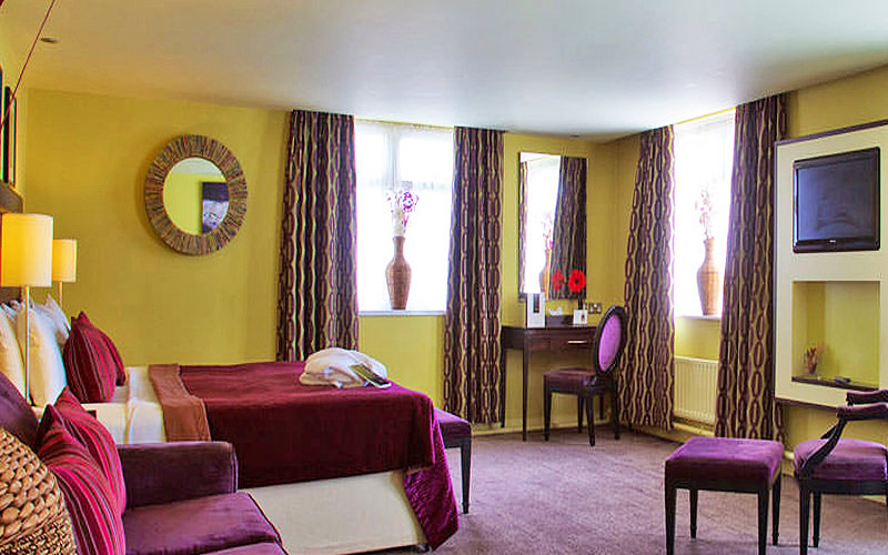 A yellow hotel room, with a purple double bed, purple chairs and a dressing cabinet along the wall