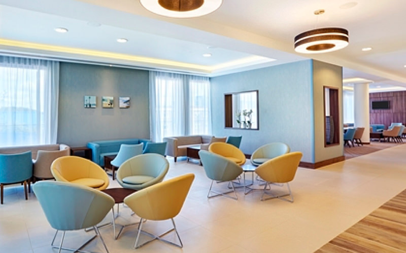 Blue and yellow chairs around circular tables in a hotel lobby