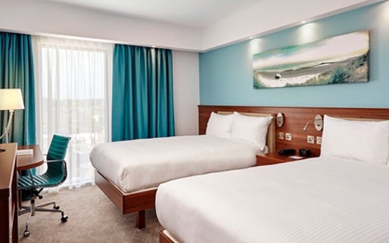 Two white single beds in a blue hotel room, facing a dressing table