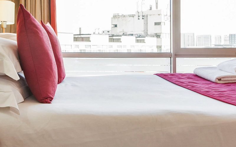 A double bed, with white cushions on top, and a city skyline out of the windows