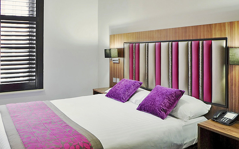 A double bed with purple cushions on top