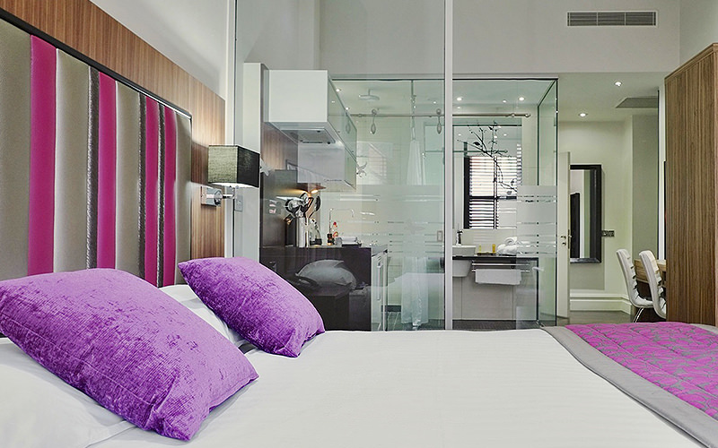 A double bed with purple cushions on top, and a glass-walled bathroom in the background