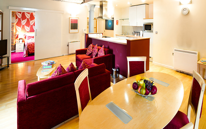 An open plan living and kitchen area, with a dining table in the foreground, and two red sofas in the backgrouund