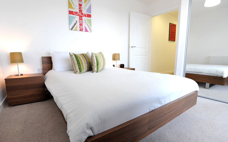 A double bed in a bedroom, with a bedside table and lamp on the side