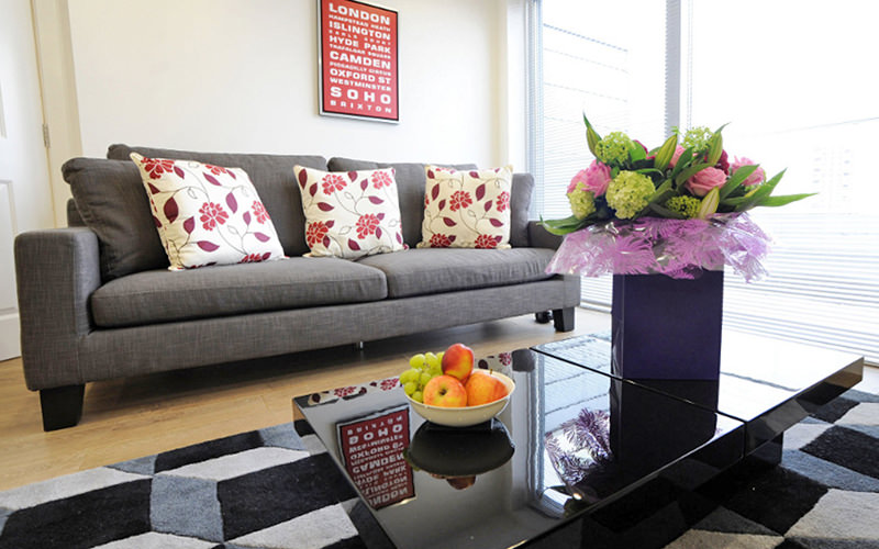 A sofa with three floral cushions, facing a coffee table topped with flowers and a bowl of fruit