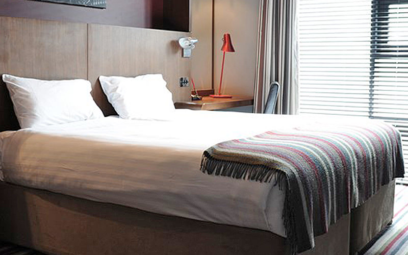 A double bed with white bed linen and a throw over the bottom of the bed