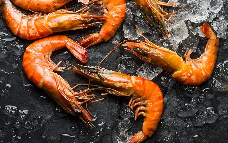 Some king prawns being cooked in a pan with ice