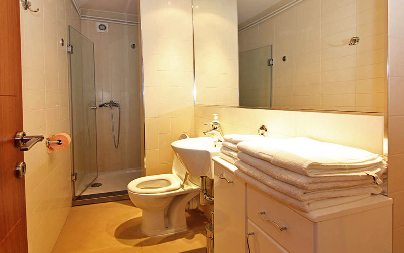 A clean white shower room with a stack of towels in the foreground