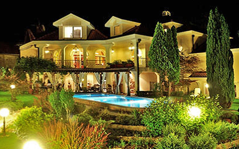Night shot of a luxury villa exterior with trees and swimming pool