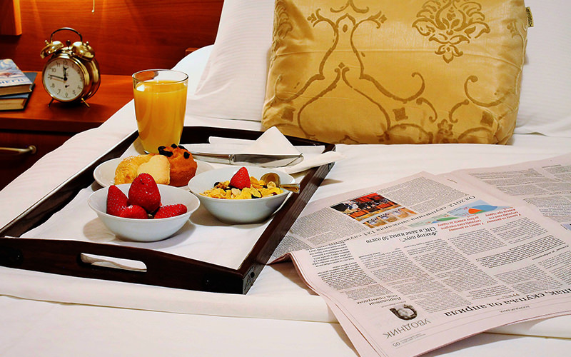 Strawberries, pastries and orange juice placed on a tray, alongside a newspaper on the bed