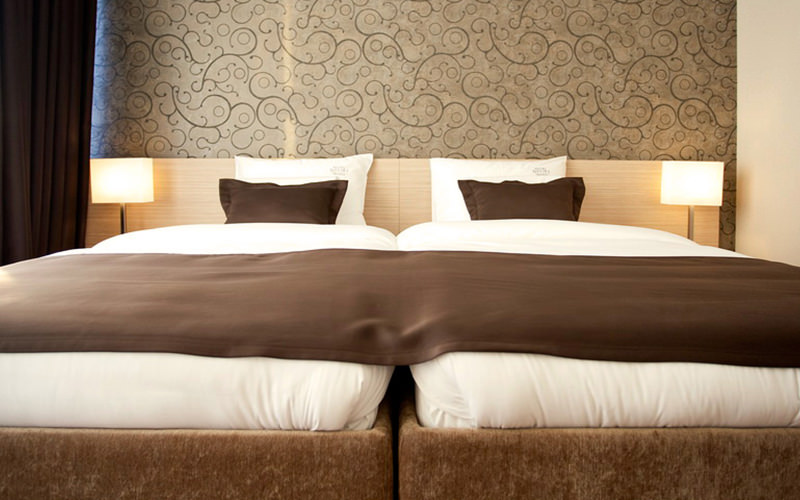 A double bed with brown and cream bedding