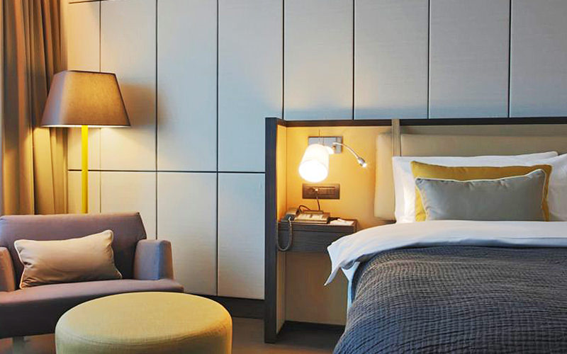 A luxury bedroom with lamp, sidetable, seat and puff stool