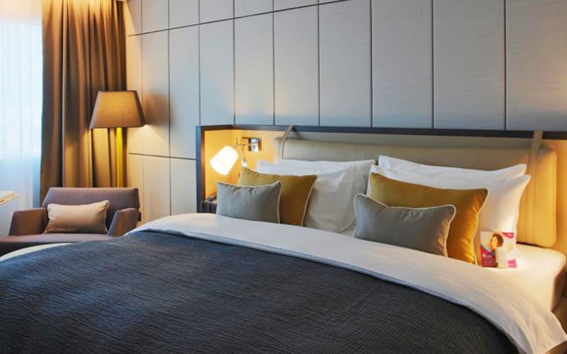 A double bed with grey and yellow bedding
