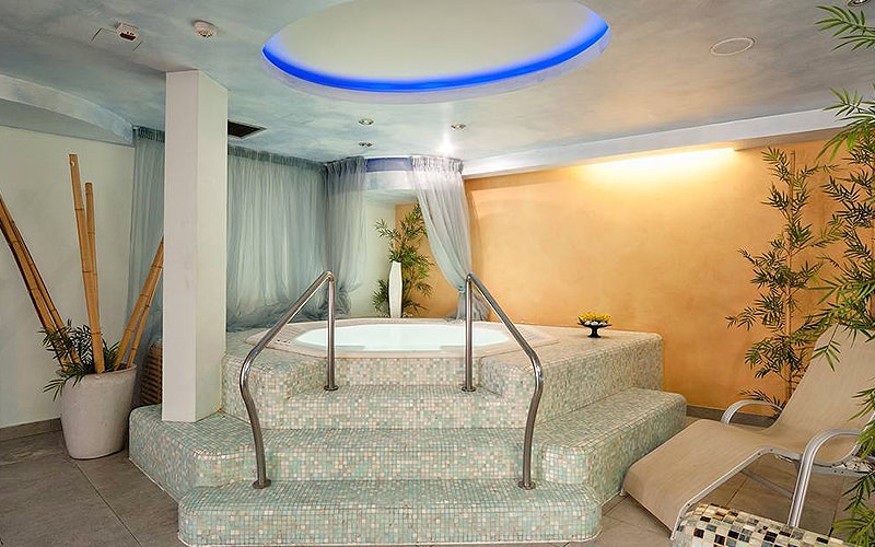 A jacuzzi with a sun lounger and bamboo shoots surrounding it