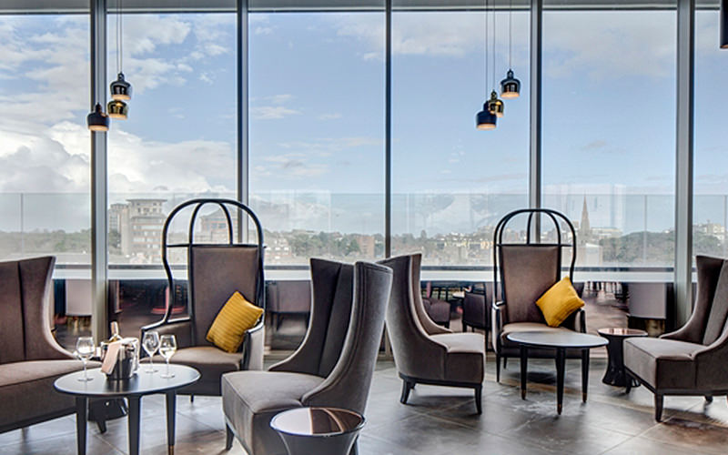 Tables and chairs in a room with floor to ceiling windows