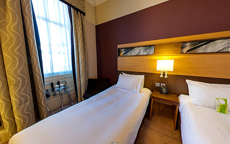 Twin beds in a room with wooden panels and a large window