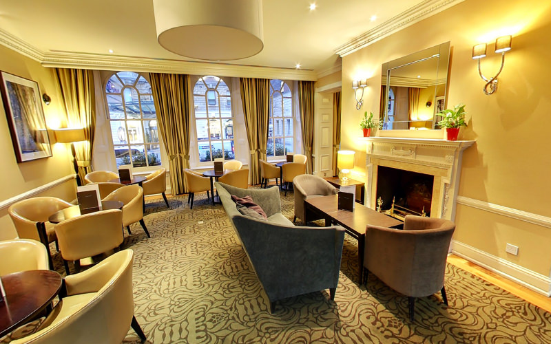 Chairs and tables in a lobby at Hilton Euston, London